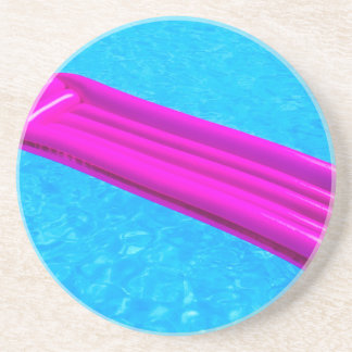 Pink air mattress on water of swimming pool drink coaster