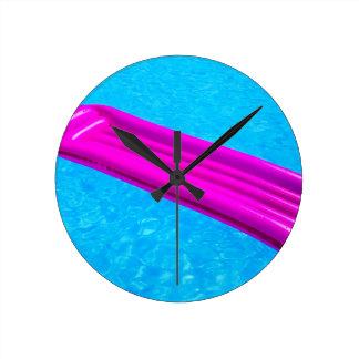 Pink air mattress on water of swimming pool wall clocks