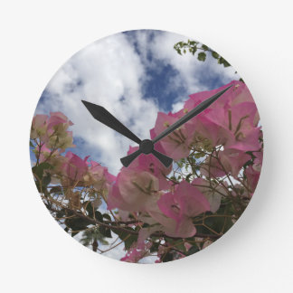 pink flowers against a blue sky round clock
