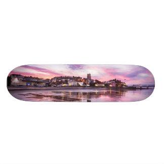 Pink sunset reflections over Cromer town at dusk Skate Board Deck