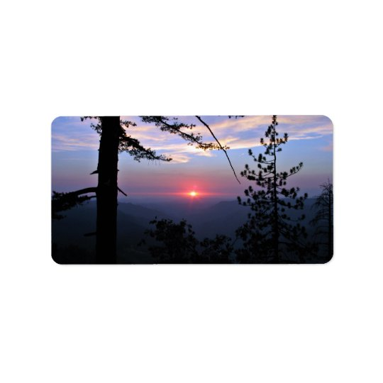 Pink sunset with pine trees and clouds label
