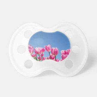 Pink tulips field with blue sky baby pacifiers