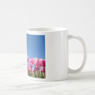 Pink tulips field with blue sky coffee mug