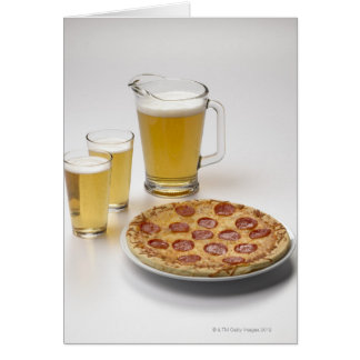 Pitcher and two pints of beer beside pepperoni card