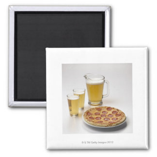 Pitcher and two pints of beer beside pepperoni square magnet