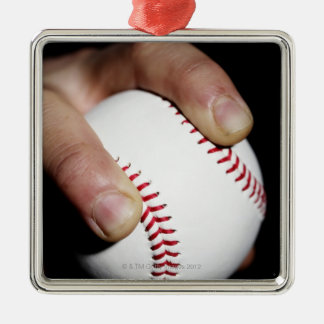 Pitchers hand gripping a baseball metal ornament