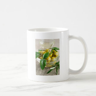 Pitted olives with green leaves and rosemary coffee mug