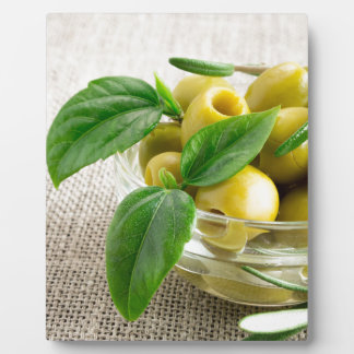Pitted olives with green leaves and rosemary plaque