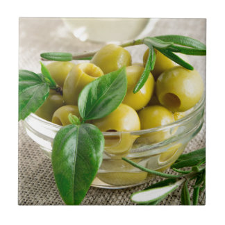 Pitted olives with green leaves and rosemary tile