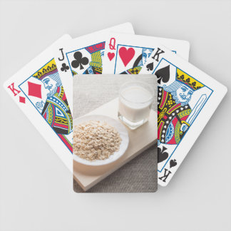 Plate with dry cereal and a glass of milk bicycle playing cards