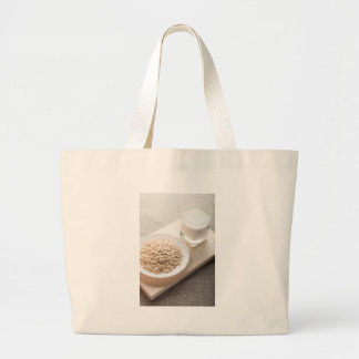 Plate with dry cereal and a glass of milk large tote bag