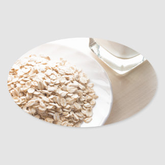 Plate with dry cereal and a glass of milk oval sticker