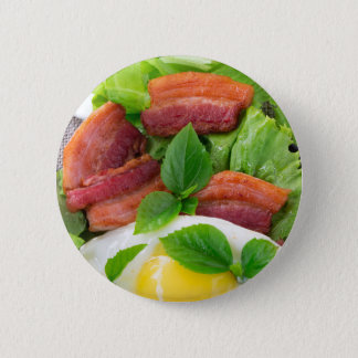 Plate with egg yolk, fried bacon and herbs 2 inch round button