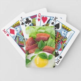 Plate with egg yolk, fried bacon and herbs bicycle playing cards