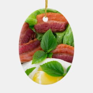 Plate with egg yolk, fried bacon and herbs ceramic ornament