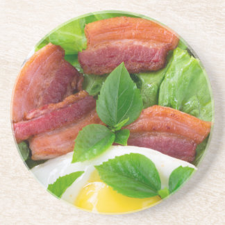 Plate with egg yolk, fried bacon and herbs coaster