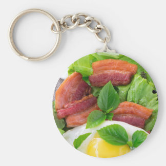 Plate with egg yolk, fried bacon and herbs keychain