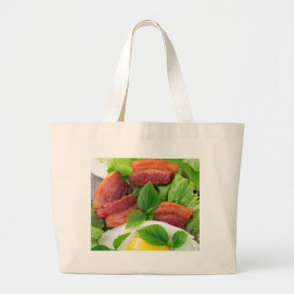 Plate with egg yolk, fried bacon and herbs large tote bag
