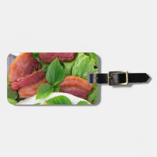 Plate with egg yolk, fried bacon and herbs luggage tag