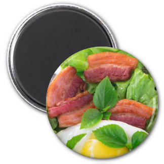 Plate with egg yolk, fried bacon and herbs magnet