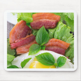 Plate with egg yolk, fried bacon and herbs mouse pad