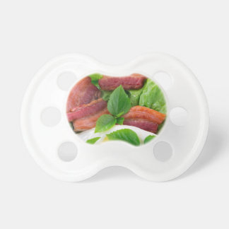 Plate with egg yolk, fried bacon and herbs pacifier