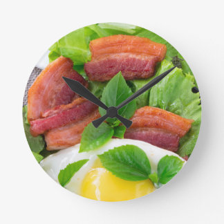 Plate with egg yolk, fried bacon and herbs round clock