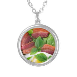 Plate with egg yolk, fried bacon and herbs silver plated necklace