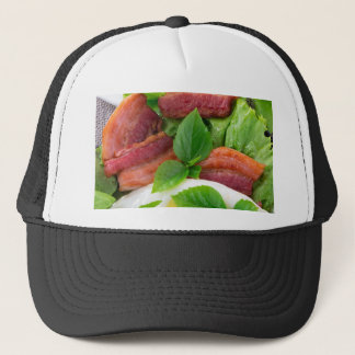 Plate with egg yolk, fried bacon and herbs trucker hat