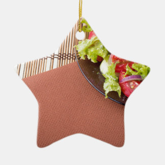 Plate with fresh salad of raw tomatoes and lettuce ceramic star ornament