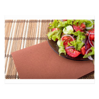 Plate with fresh salad of raw tomatoes and lettuce postcard