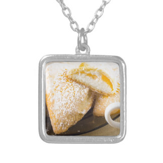 Plate with sweet pastries with sweet cheese silver plated necklace