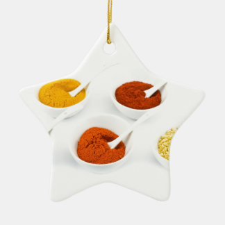 Porcelain bowls and spoons with various spices ceramic ornament