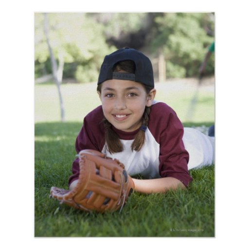 Portrait of girl lying on ground with baseball poster
