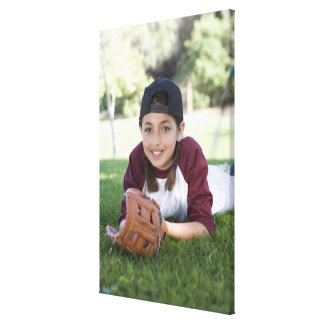 Portrait of girl lying on ground with baseball stretched canvas print