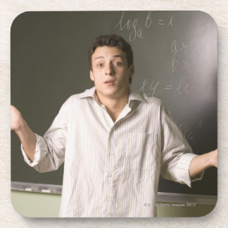 portrait of male student in front of blackboard beverage coaster