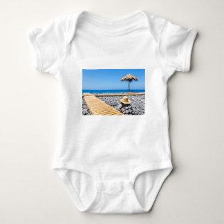 Portuguese stony beach with path sea hat parasols baby bodysuit