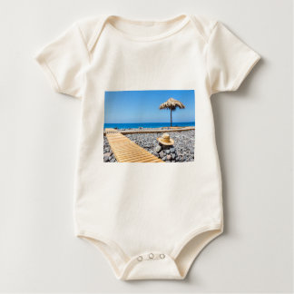 Portuguese stony beach with path sea hat parasols baby bodysuit
