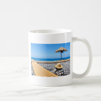 Portuguese stony beach with path sea hat parasols coffee mug