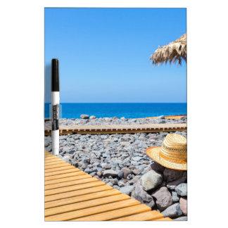 Portuguese stony beach with path sea hat parasols dry erase board