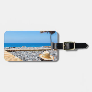 Portuguese stony beach with path sea hat parasols luggage tag