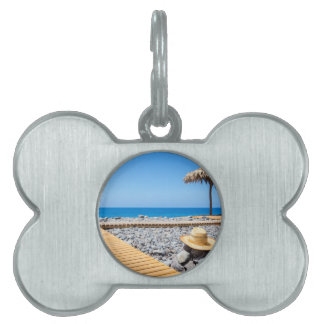 Portuguese stony beach with path sea hat parasols pet ID tag