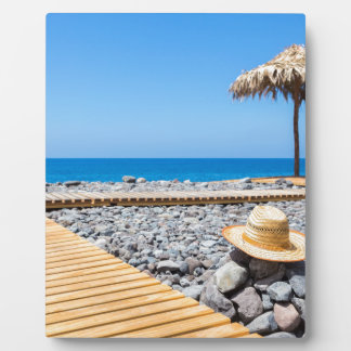 Portuguese stony beach with path sea hat parasols plaque