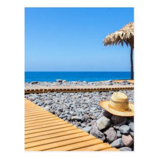 Portuguese stony beach with path sea hat parasols postcard