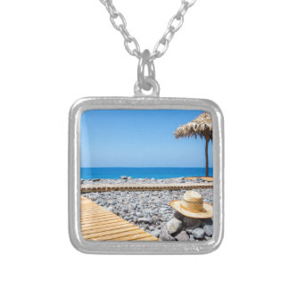 Portuguese stony beach with path sea hat parasols silver plated necklace