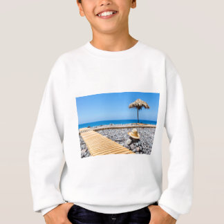 Portuguese stony beach with path sea hat parasols sweatshirt
