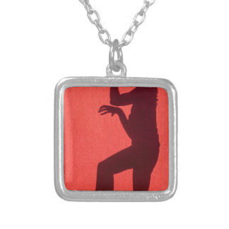 Profile shadow of woman on red wall silver plated necklace