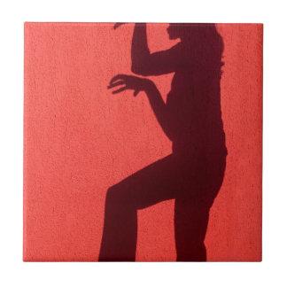 Profile shadow of woman on red wall tile