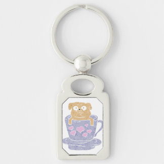 Pug dog sitting in purple  cup with heart. Silver-Colored rectangle keychain