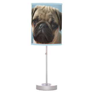 Pug puppy sitting on bed table lamp